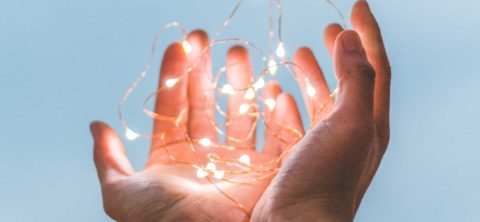 Close up of hands holding fairy lights.