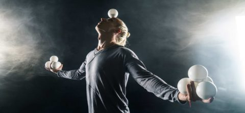 young man juggling white balls, balancing on on his head.